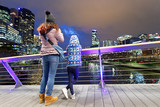Mother and daughter at night photographing city skyline from beautiful modern bridge - 224334255