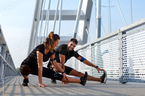 Fototapeta Young couple doing morning workout outdoors. Young man and woman stretching they muscle before running on bridge.