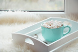 Blue cup of hot chocolate with marshmallow on windowsill with furskin for relax. Holiday concept. Home style.