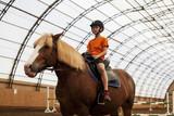 Boy in helmet learning Horseback Riding - 224344226