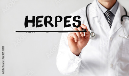 Doctor writing word HERPES with marker, Medical concept
