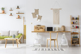 Real photo of a natural home office interior desk organizer, macrame on a wall, shelves and couch - 224367059