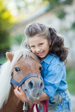 A small smiling girl with curly hair dressed in jeans walking with a pony at the stable - 224368800