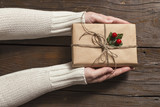 Female hands holding a Christmas present - 224370631