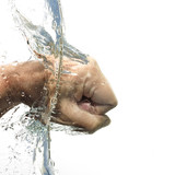 human fist beats through the water with splash, isolated on a white background, copy space - 224377883