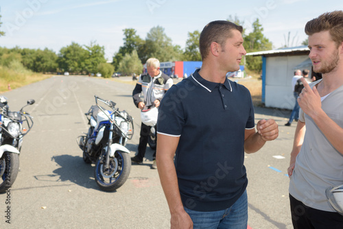 young man with instructor during motorbike lesson