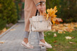 Stylish beautiful woman walking on the street wearing a beige coat, a bag, a warm sweater, a fashionable outfit, an autumn trend, accessories