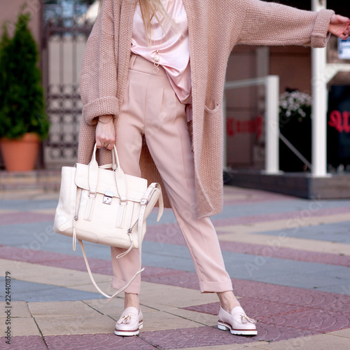 Young beautiful stylish woman walking in a pink coat, holding a bag in hands, street style, spring autumn trend, light pants