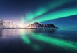 Leinwandbild Motiv Northern lights in Lofoten islands, Norway. Green Aurora borealis. Starry sky with polar lights. Night winter landscape with aurora, sea with sky reflection, rocks, beach and snowy mountains. Nature