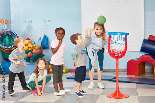 Kinder werfen Basketball in ein Netz