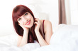 Beautiful smiling young woman lying on bed at home
