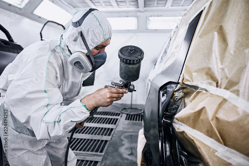 Leinwanddruck Bild Painting the car in black color in the paint chamber on the service..