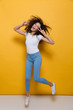 Quadro Full length photo of joyful woman 20s with curly hair rejoicing and jumping, isolated over yellow background