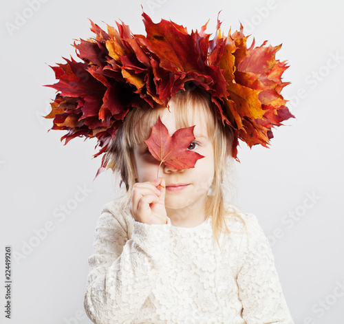 Cute child girl in autumn leaves on head, portrait