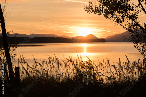 sunset over lake with mountains in the background