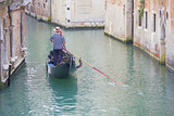 Venetian gondolier in the gondola is transported tourists through canal waters of Venice Italy