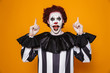 Quadro Happy clown man 20s wearing black costume and halloween makeup looking at camera, isolated over yellow background