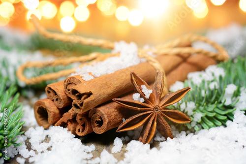 Leinwanddruck Bild Cinnamon sticks as a spice for Christmas with fairy lights as decoration and lighting