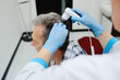 baldness. doctor examines an elderly man hair using special equipment - trihoskopa