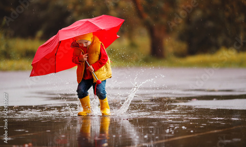Leinwandbild Motiv happy child baby boy with rubber boots and umbrella jump in puddle  on autumn walk