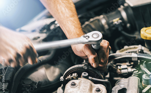 Hands of car mechanic in auto repair service with wrench - 224511004