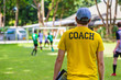 Male soccer or football coach standing on the sideline watching his team play