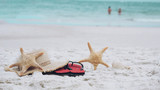 Summer vacation and holiday concept, starfish, beach hat and sea shell on sandy beach, green sea . - 224542039