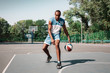 Picture of young confused african basketball player practicing outdoor. Fit afro man in motion and movement. athletic and sport lifestyle concept