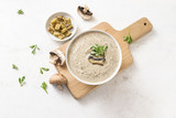 mushroom cream soup with herb garnish and croutons on a light  background with copy space, high angle view from above - 224563265