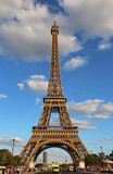 Very high Eiffel Tower and the blue sky with clouds