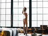 Silhouette woman at the window against a background of sun rays in the morning. Christmas concept