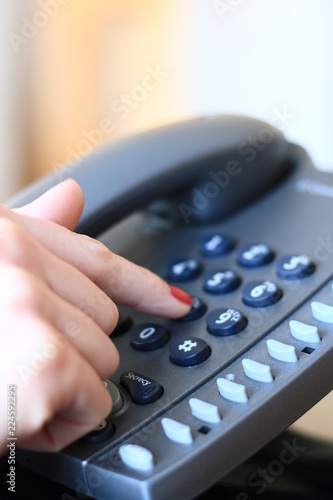 Receptionist dialing a number - 224592295