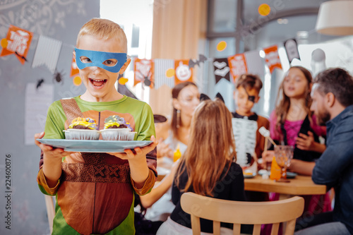 Leinwanddruck Bild Ninja turtle. Blonde-haired schoolboy wearing Ninja turtle costume for Halloween looking extremely happy and funny
