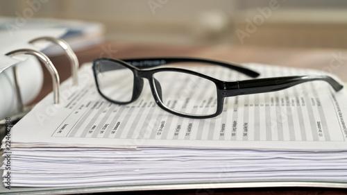 fototapeta na ścianę Brille auf einem Aktenordner in einem Büro