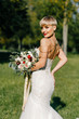fashionable bride with short hair with a big bouquet posing in the park