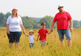 Overweight parents with her children walking together. Family enjoying life on countryside. - 224614285