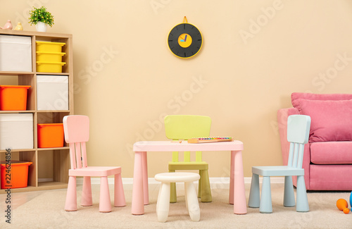 Leinwandbild Motiv Cozy kids room interior with table, sofa and shelving unit