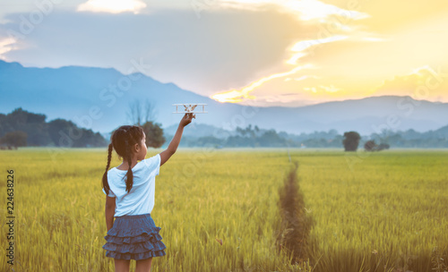 Leinwanddruck Bild Cute asian child girl playing with toy wooden airplane in the field at sunset time in vintage color tone