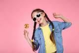 Young girl with lollipop and sunglasses on pink background