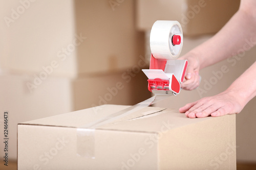 Leinwanddruck Bild Female hands packaging cardboard box with dispenser