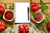 tomato ketchup.Tomato sauce.The recipe for ketchup.  home made sauce ketchup in two white plates,  ripe red tomatoes with leaves, basil, marjoram and an empty notebook on a wooden table. - 224648890
