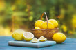 Quadro Fresh, ripe lemons in wicker basket. Green nature in background.