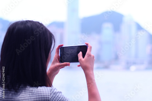 Woman is taking photo with smart phone of city view in Hong Kong.