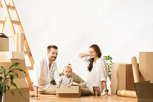 Couple moving to a new home. Happy married people with newborn child buy a new apartment to start life together. The family at repair and relocation planing to accommodation against boxes - 224680815