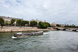 Paris, France - August 16, 2017. View of medieval Cite island and Pont au Change bridge from Seine riverside. Popular french landmark and tourist cruise boat in river Seine.