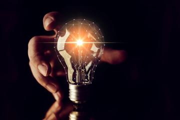 man hand choose glow light bulb creativity business ideas concept black background © whyframeshot