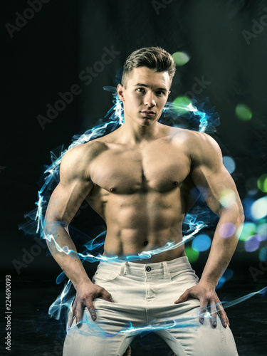 Young handsome man with muscular shirtless torso in white denim and glowing blue spiral line looking at camera © theartofphoto