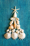 Christmas tree made from sea shells and starfish on wooden blue background, top view - 224694624