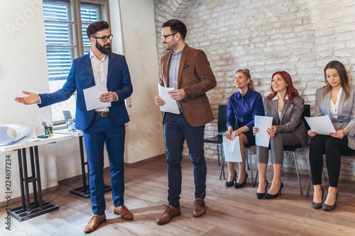 Foto Murales Businessman  with candidate next to  people waiting for job interview in a modern office