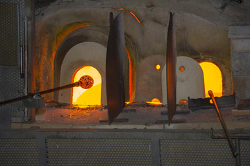 Manufacturing glass in a traditional oven, in glass factory in Murano, Venice, Italy